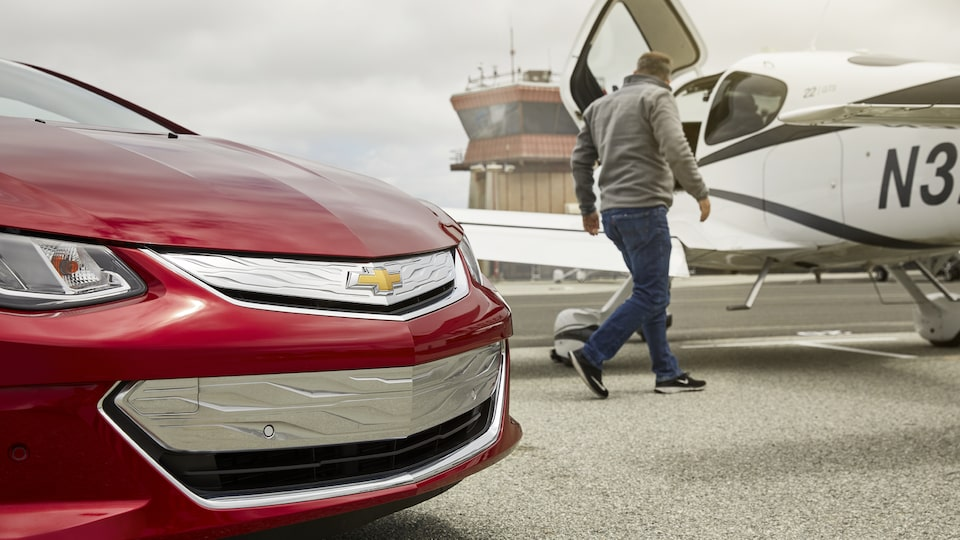 A man walks toward a small airplane, with the grille of a Volt in the foreground.