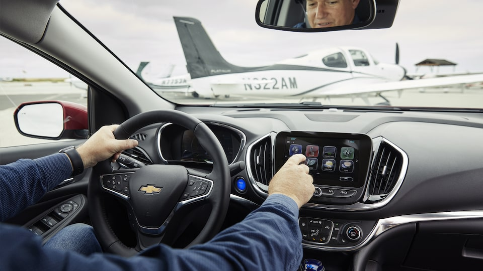A man interacts with the touch-screen inside the Chevrolet Volt.