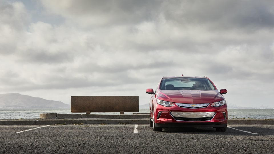 The front of a Chevrolet volt parked backwards near the shore.