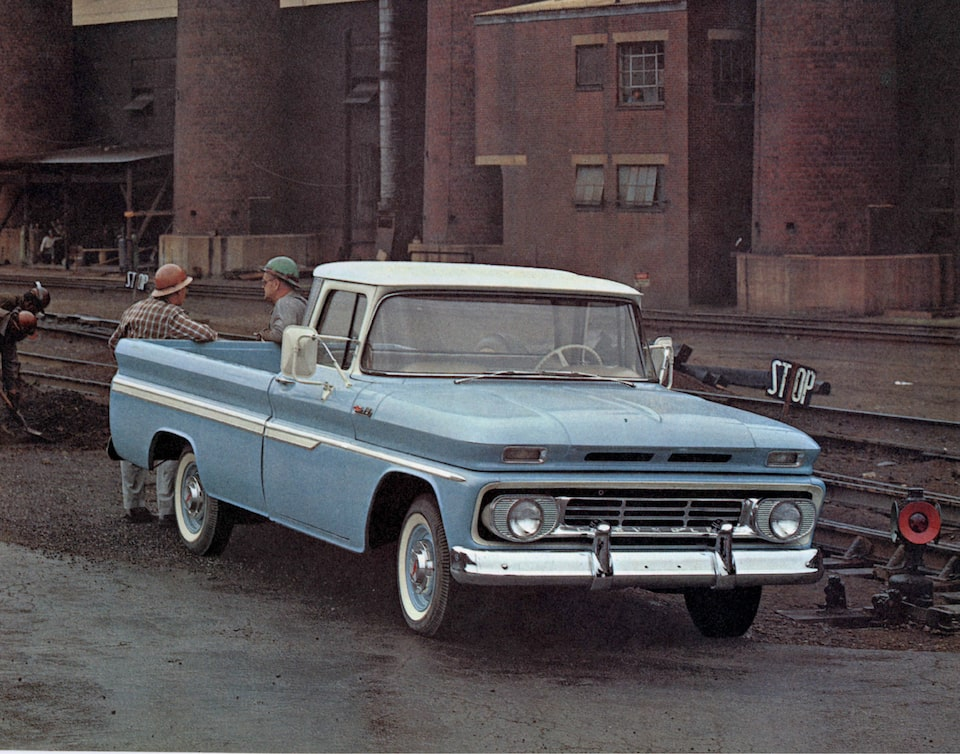 An old photograph from the 1962 C/K Series truck brochure of a light blue pickup from the C/K Series with two men standing behind the bed.