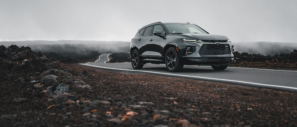 A gray Chevrolet Blazer drives on a narrow strip of pavement through a field of black lava rocks in Hawaii.