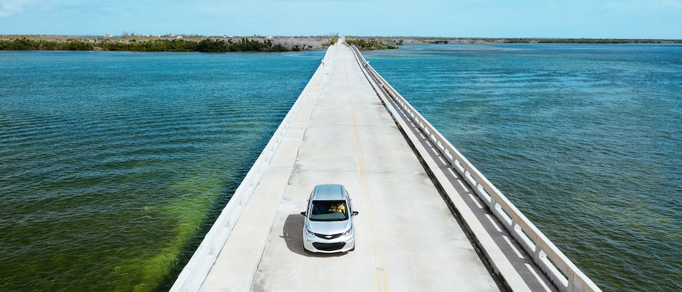A Silver Ice Metallic Bolt EV drives across a causeway in the Florida Keys, with the ocean on both sides and an island in the background.