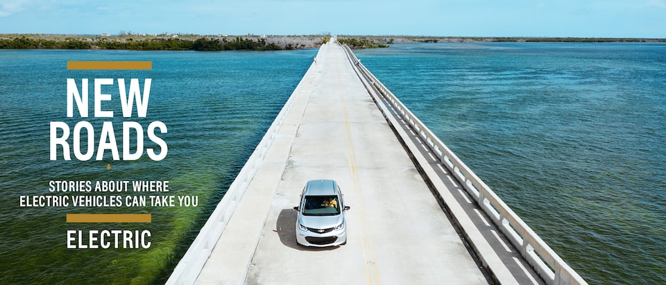Seen from above, a Silver Ice Metallic Bolt EV drives across a causeway in the Florida Keys. Text over image reads: New Roads. Stories about where electric vehicles can take you. Electric.