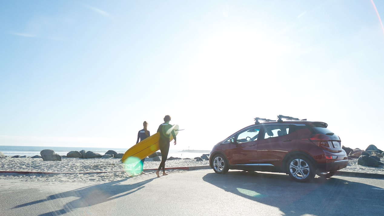 Two people in wetsuits walk from a parking lot out onto an ocean beach carrying a surfboard. A red Chevrolet Bolt EV sits in the parking lot.