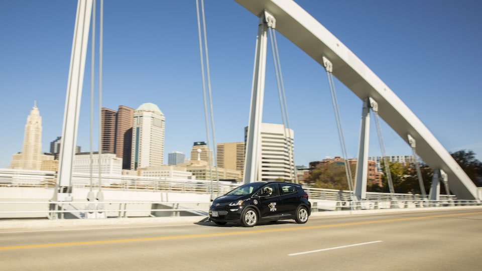A Bolt EV taxi drives across a bridge.