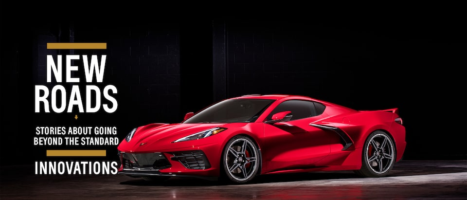 A red mid-engine 2020 Corvette sits in a spotlight against a black background.