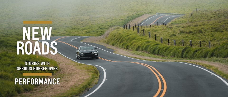 A black 2020 Camaro SS drives on a winding and hilly two-lane road.