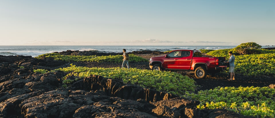 Two people stand near a red Chevrolet Colorado ZR2 parked in a rocky area with low brush next to the ocean in Hawaii.