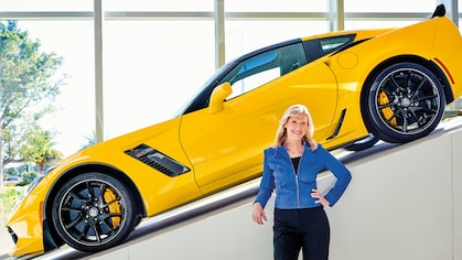 Hertz CEO Kathy Marinello with a yellow Chevrolet Corvette displayed on a ramp behind her.