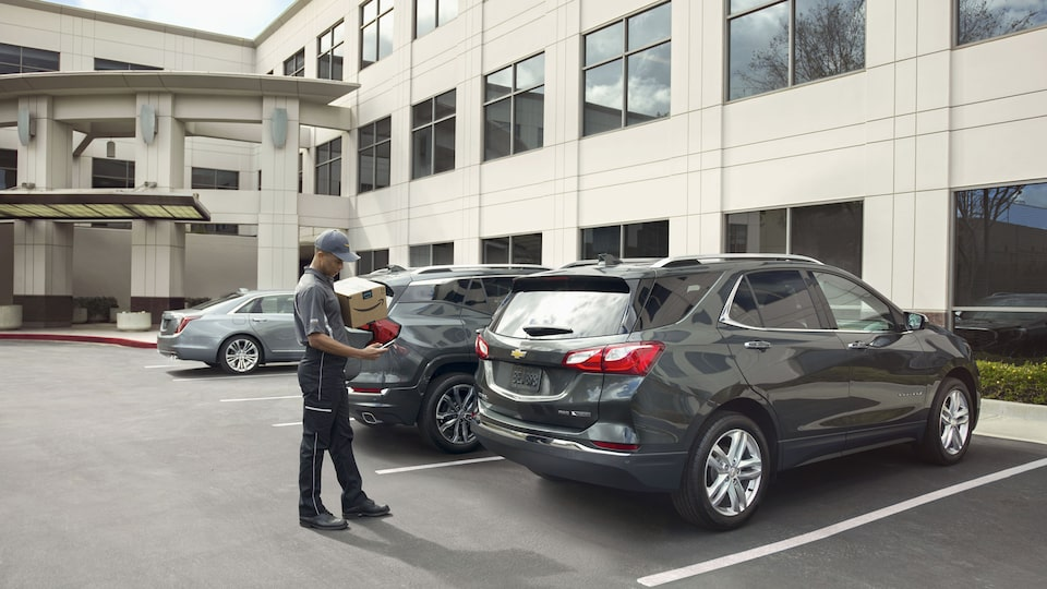 A delivery man delivers an Amazon package to a Chevrolet Equinox.