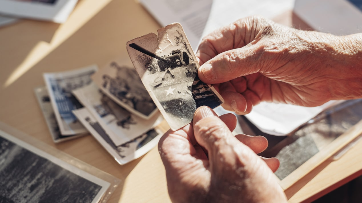 George Patton Waters' hands holding an old picture of a tank, with other old photos on the table below.