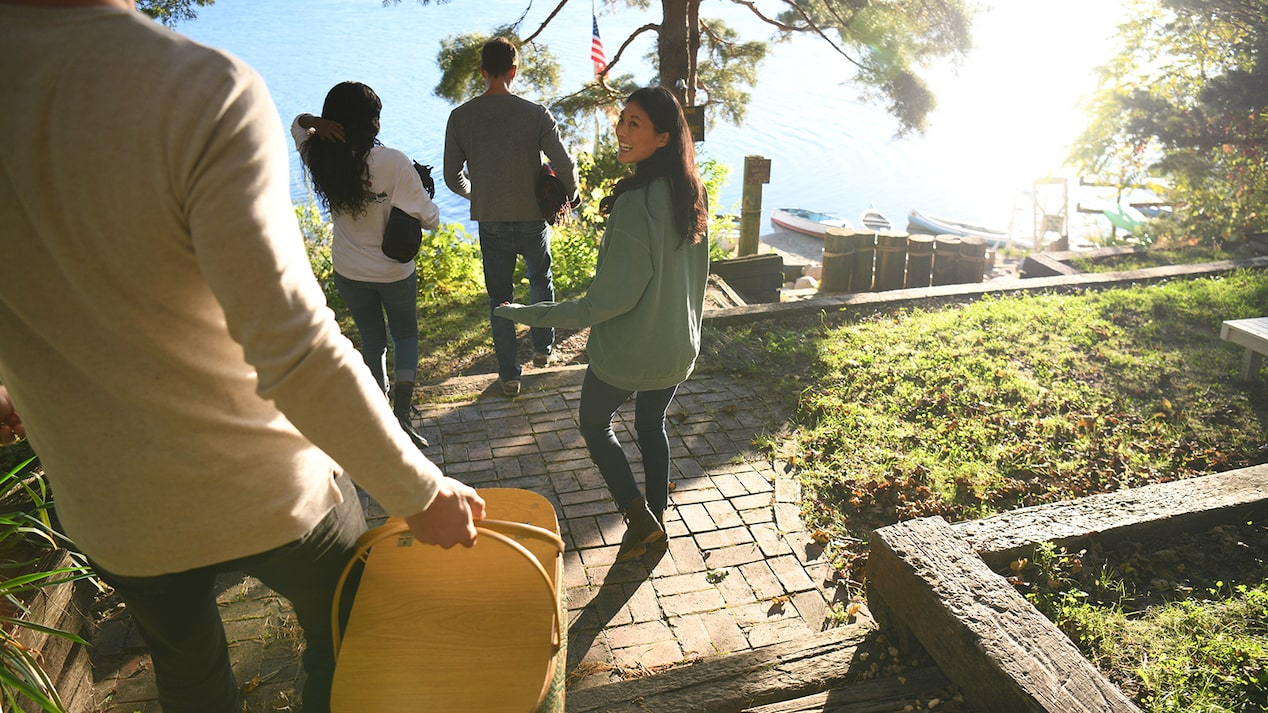 A woman with a picnic basket walks down the stairs with three friends toward Lake Wandawega.