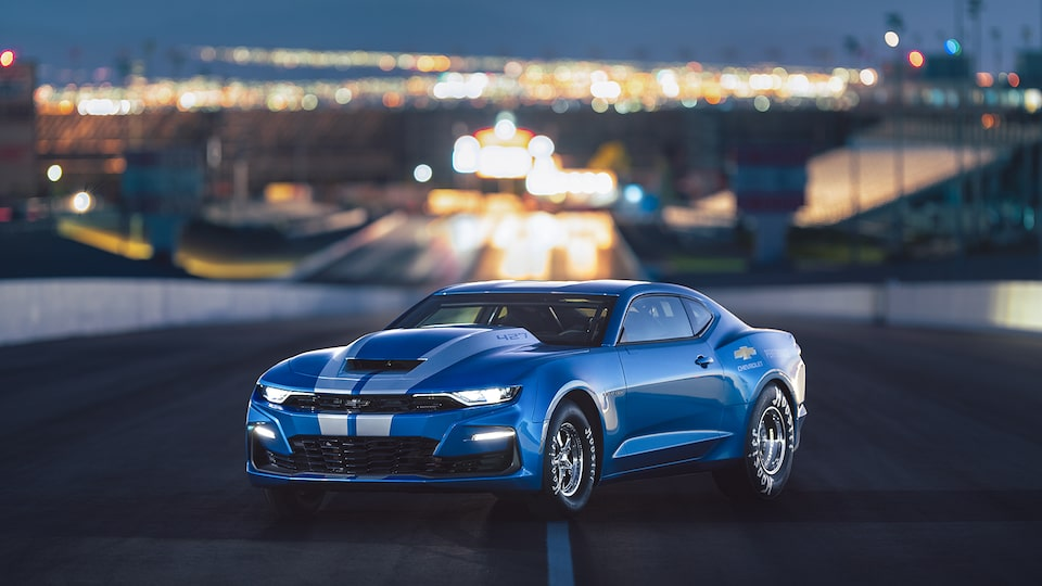 A blue COPO Camaro on an empty road with city lights in the background.