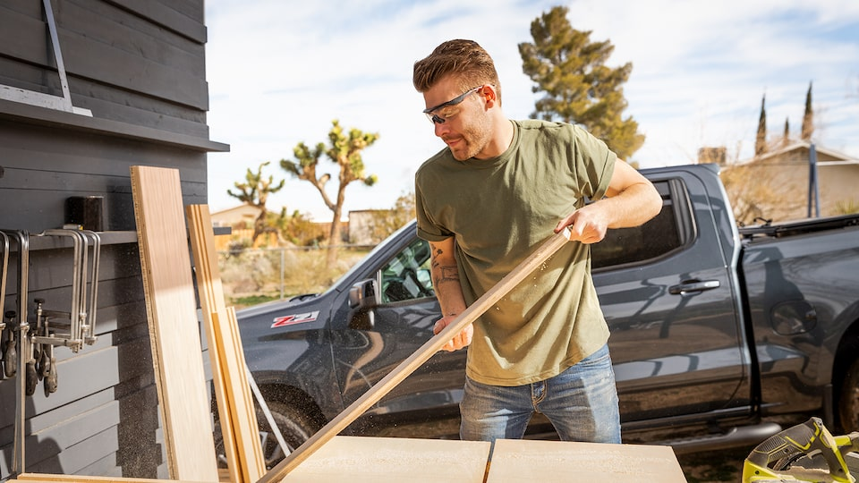 A man wearing work clothes and safety glasses moves lumber in front of a black Chevy Silverado pickup.