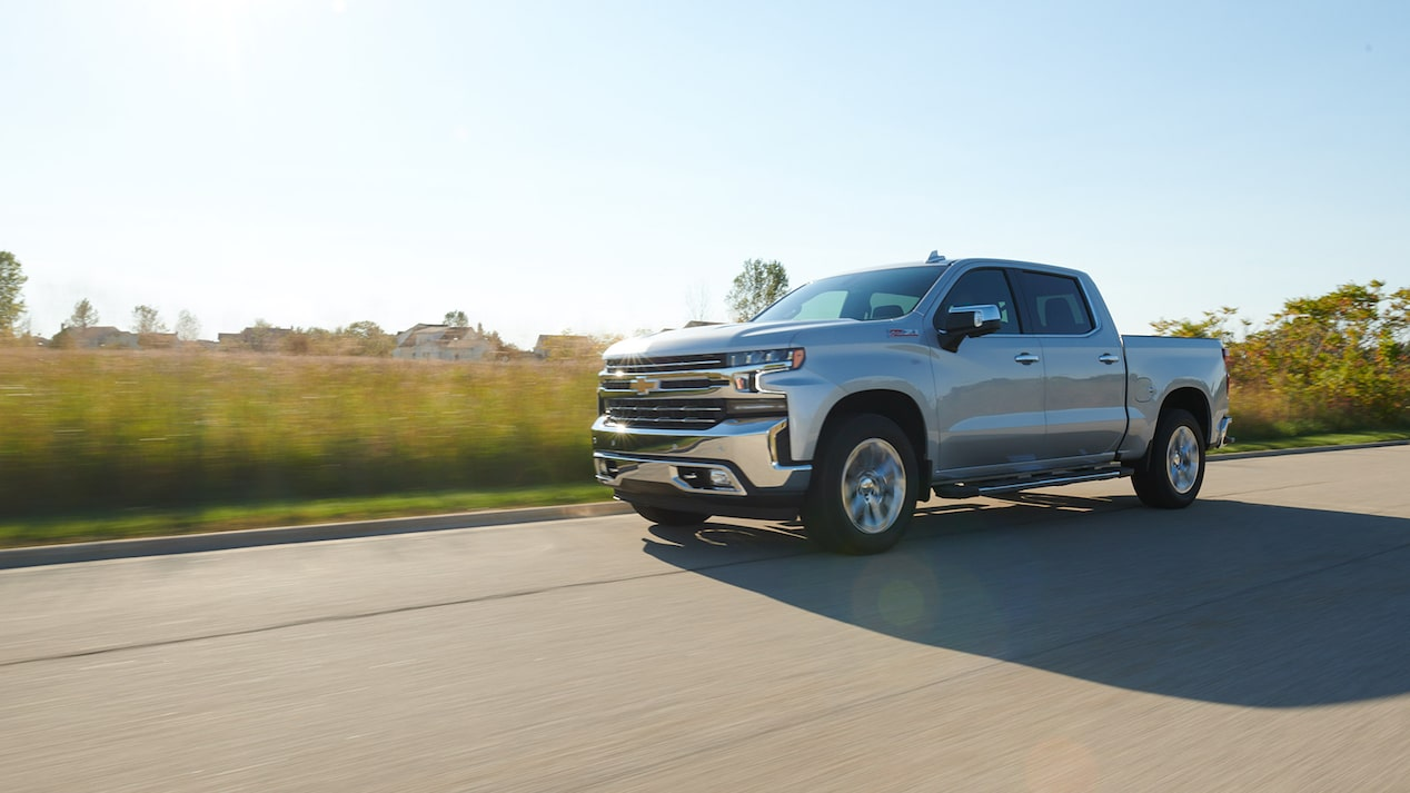 A silver All-New Silverado pickup driving down a road with fields in the background.