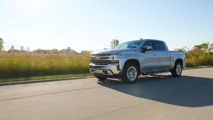 A silver All-New Silverado drives down a dirt road through a field with dust behind it.