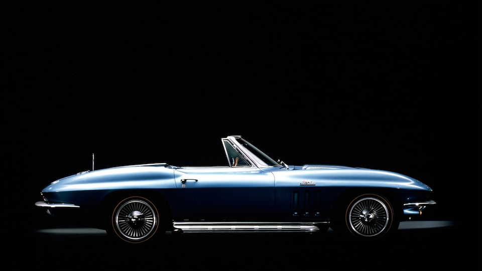A Generation 2 (C2, 1963-1967) blue Corvette Convertible with the top down seen from the side against a black background.