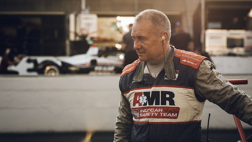 "Tim Baughman wears a safety suit that reads ""AMR IndyCar Safety Team."" There is a race car and other equipment in the background."