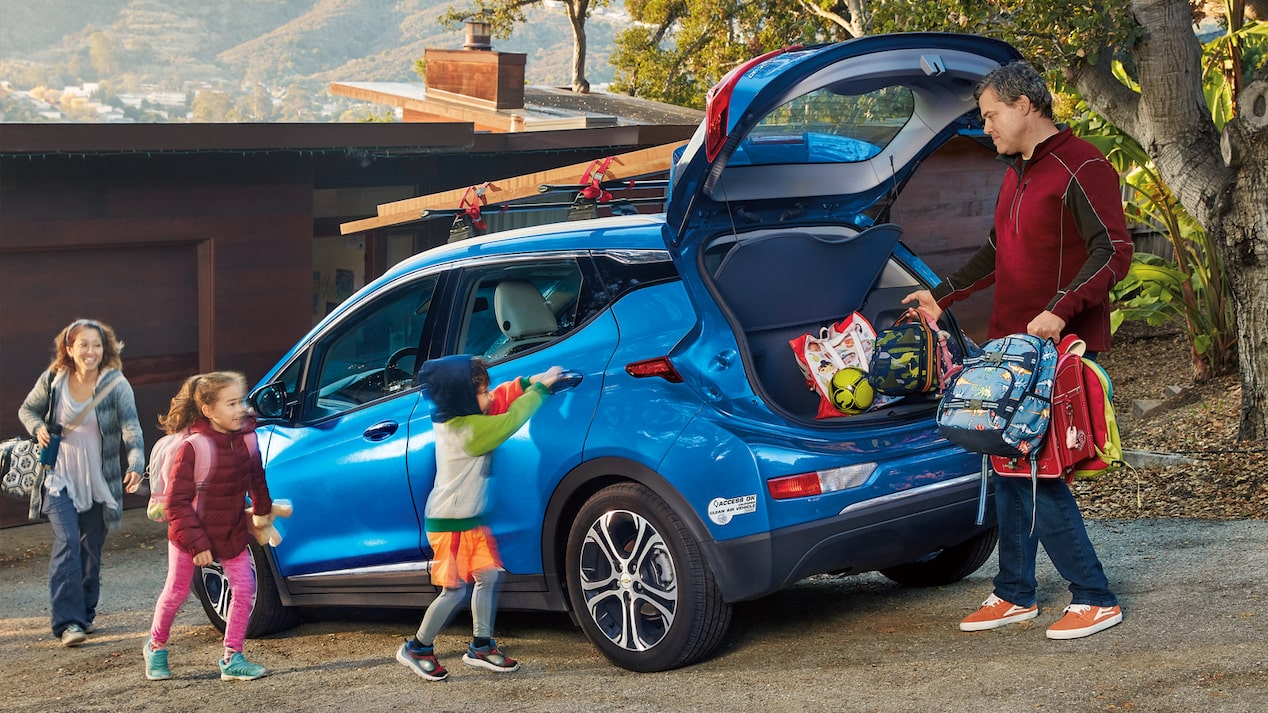 Ethan Stock with his wife and two kids loading things into the back of their blue 2017 Chevy Bolt EV.