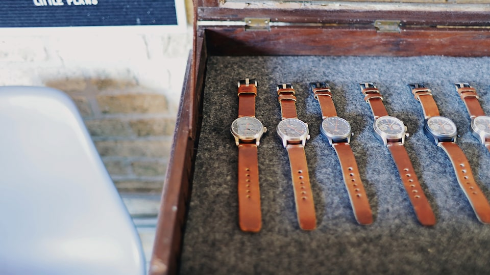A row of watches with brown leather straps sits in a felt-lined wooden box.