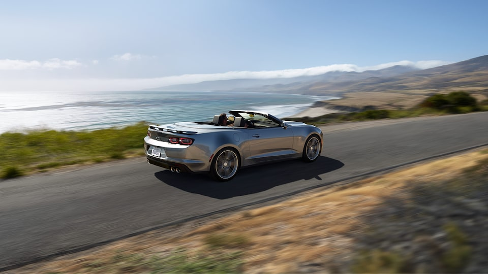A Silver Ice Metallic Camaro Convertible driving down a road high above the ocean with mountains in the distance.