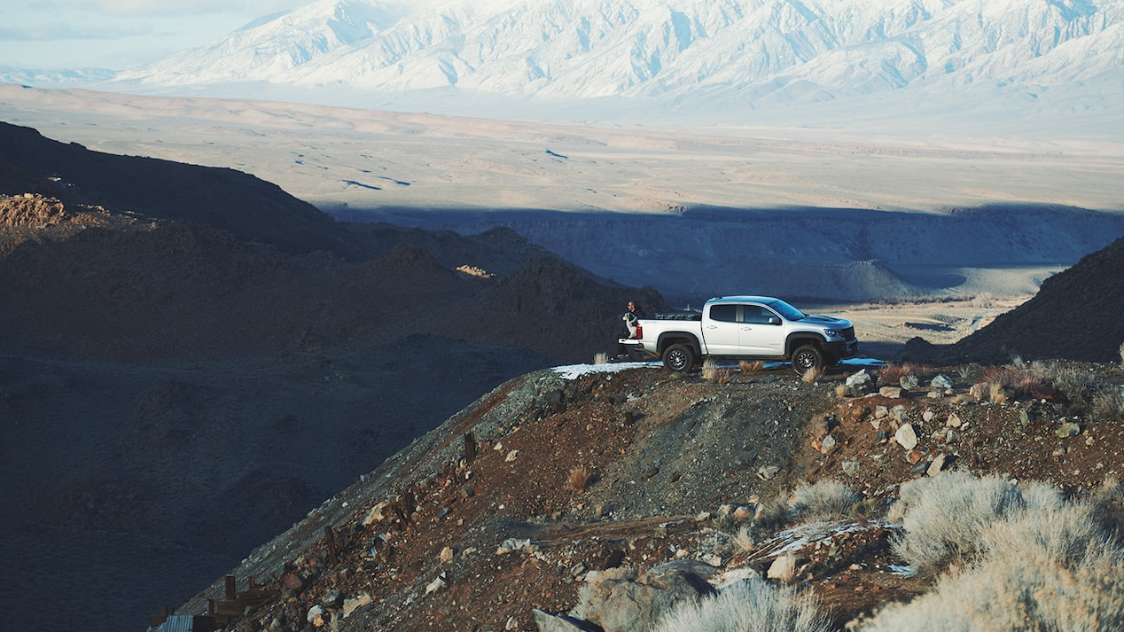 A silver Chevy Colorado ZR2 Bison pickup truck sits on a high ledge atop a hill in the California mountains, with the desert and mountains in the background.