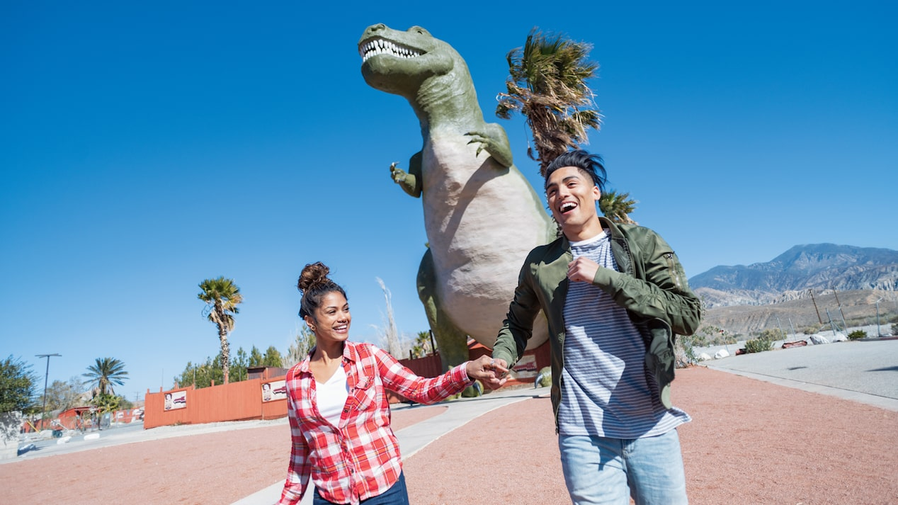 A couple holding hands in front of one of he Cabazon Dinosaurs.