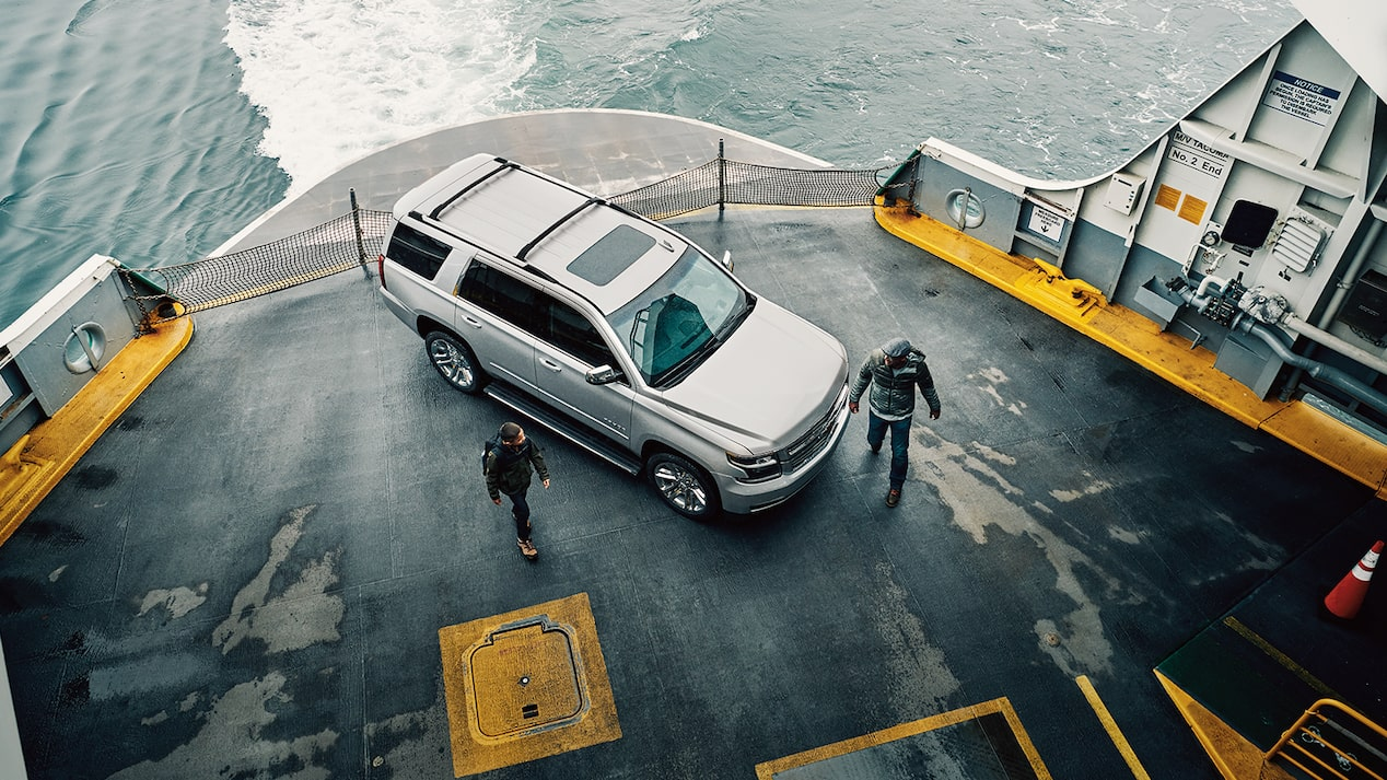 A son and father walking past a Chevy Tahoe SUV on the deck of a ferry that's underway.