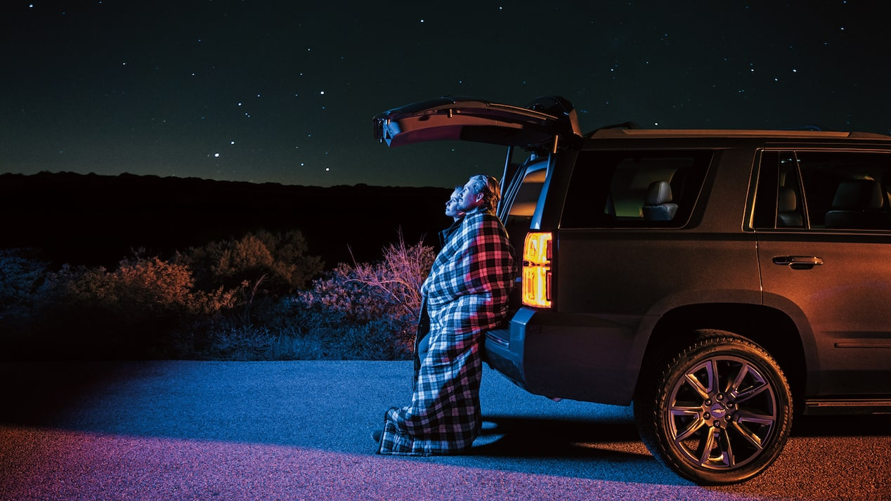 Two people standing under the open back hatch of a 2018 Chevy Tahoe, wrapped in blankets and gazing up at the star-filled sky.
