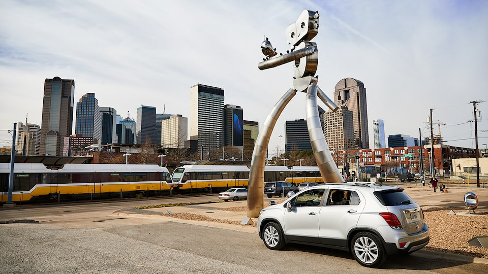 A silver Chevrolet Trax on a street next to a modern sculpture with the Dallas skyline in the background.