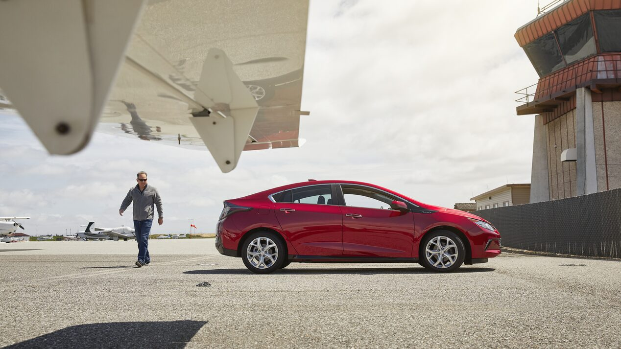 Entrepreneur Eli MurrayMetzger stands next to a Chevrolet Volt and an airplane.