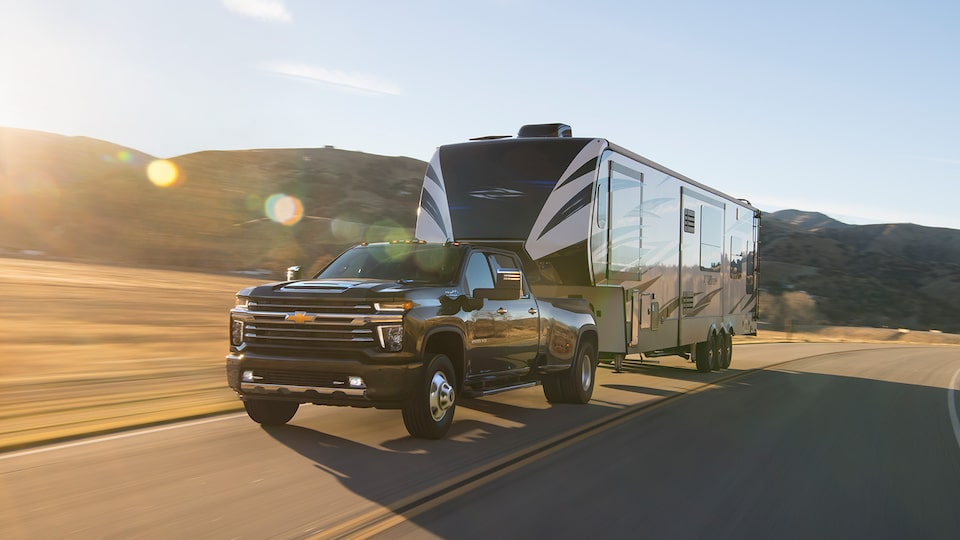 A 2020 black Silverado HD pickup hauls a large travel trailer down a two-lane road with hills in the background.