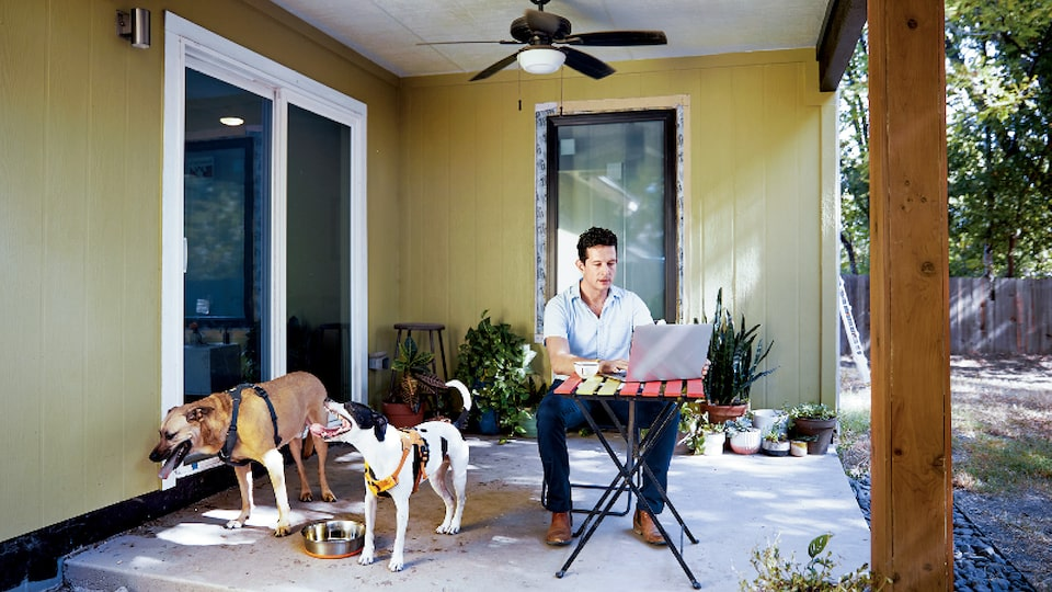 Architect Jon Hagar uses a laptop while sitting at a table on a covered outdoor patio with his two dogs standing nearby.
