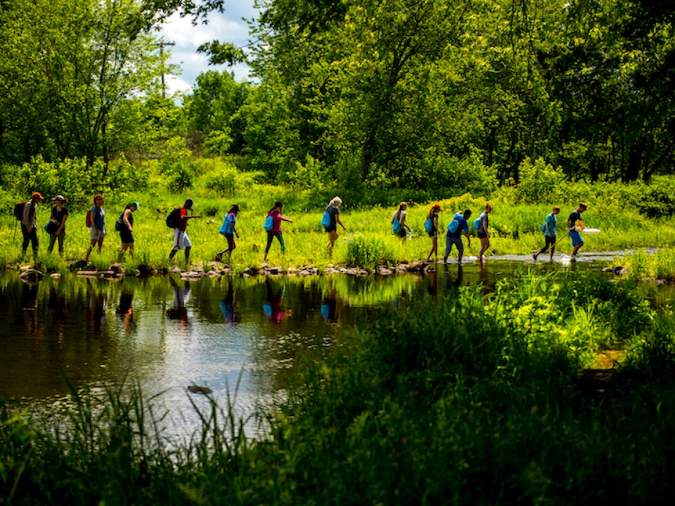 A group of students from the University of Maine Stormwater Management and Research Team walk in a single-file line next to a pond.