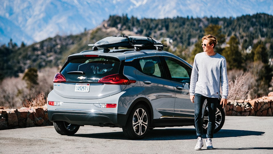 Kevin Schulz walks away from a Bolt EV parked on the side of a mountain road with a surfboard and snowboard strapped to the roof rack on top.