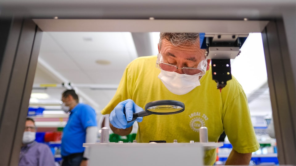 A man wearing gloves and a face mask leans over to look at a piece of equipment through a magnifying glass.