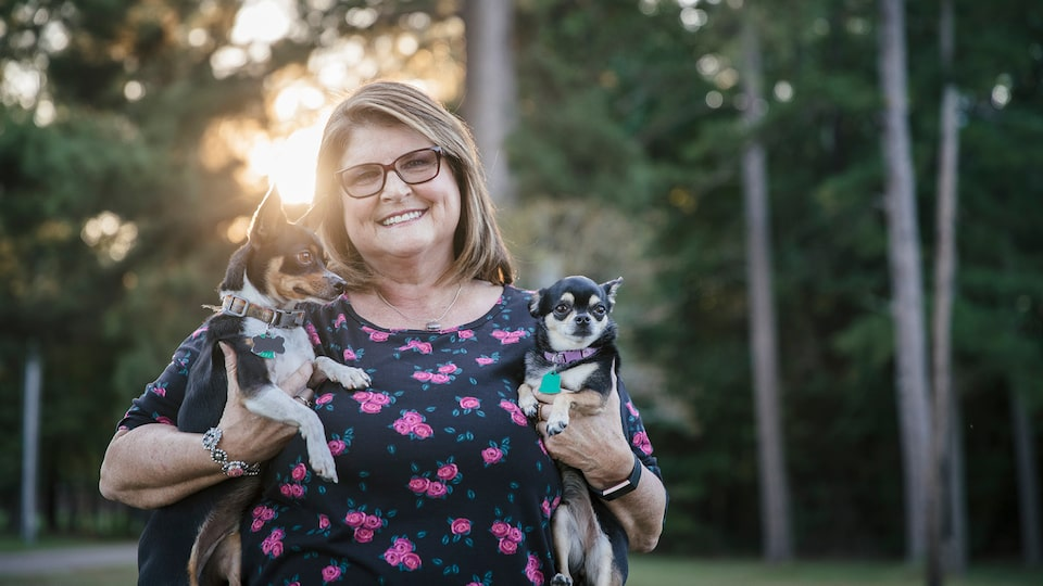 OnStar Member Teresa Moore, who was helped by OnStar after a severe crash, smiles as she holds her two small dogs.