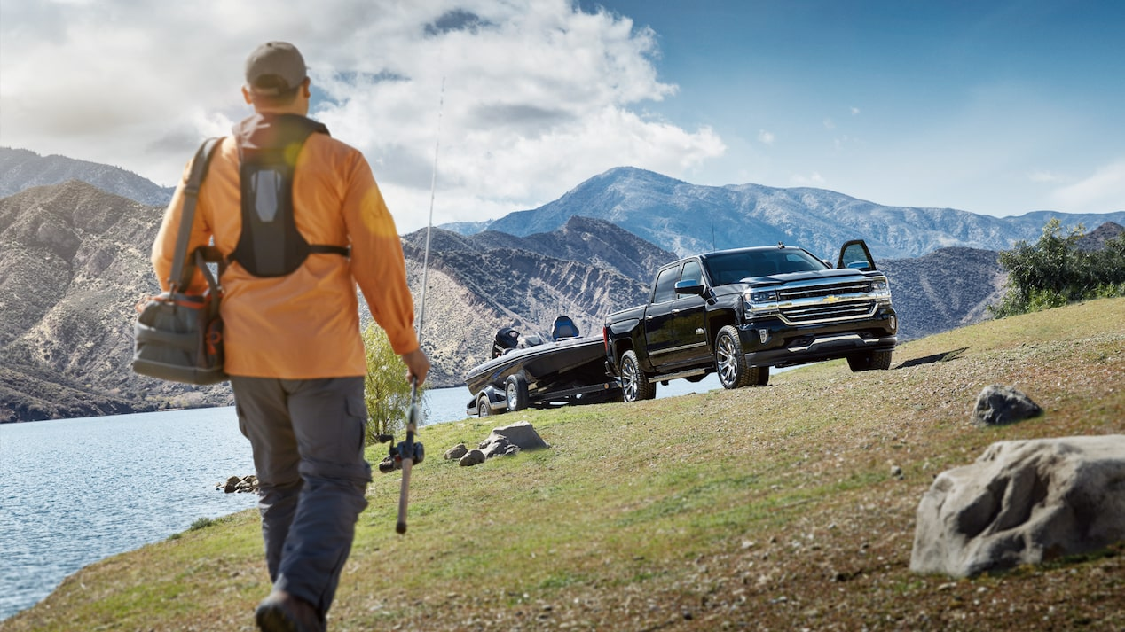 A fisherman walks along the edge of a lake toward his Chevy Silverado.