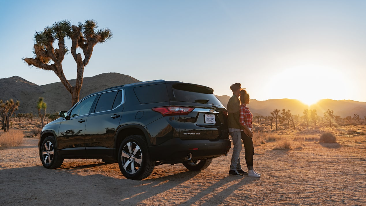 A couple watches the sunset in front of a Chevrolet Traverse.