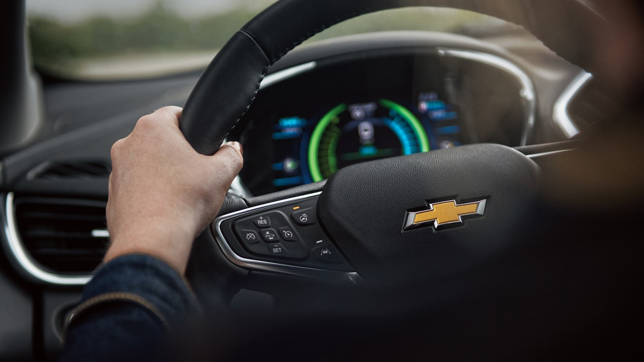The steering wheel of a Chevrolet Volt with the dashboard display behind it.