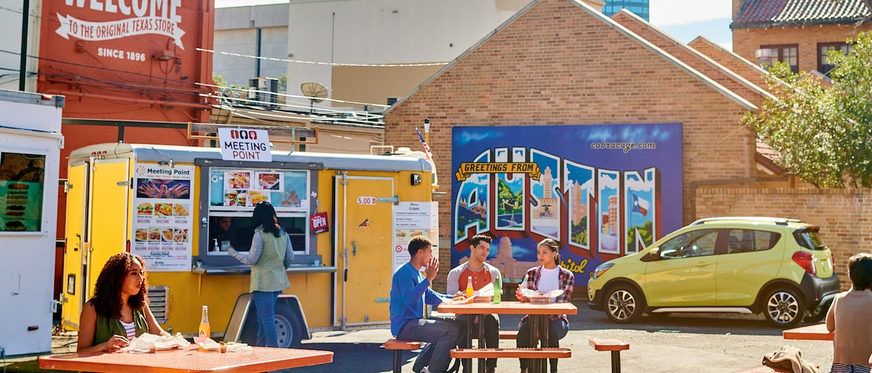 Several people eating at  tables at the University Co-op food truck area in Austin, Texas, with a yellow 2018 Chevy Spark in the background.
