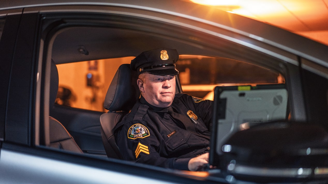 Sargent Richard Hartnett behind the wheel of his department's Chevrolet Bolt EV police vehicle.