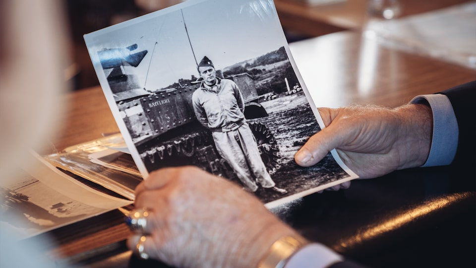 George Patton Waters' hands holding an old picture of Reuben Schaetzel as a young soldier.
