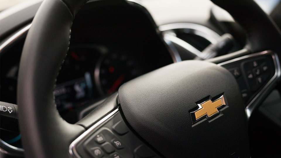 Close-up shot of the Chevrolet bow tie on the Malibu's steering wheel.