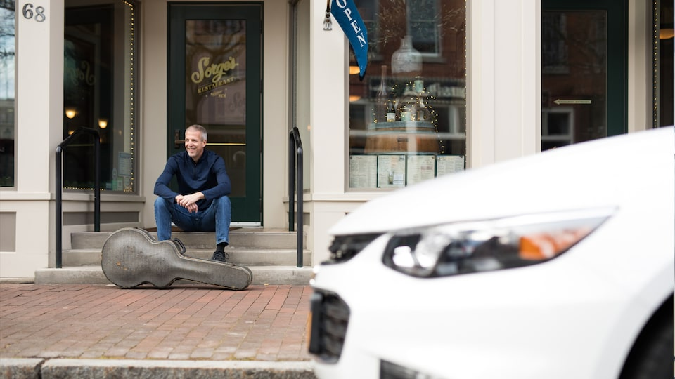 Mike Lucey sitting on a bench with his guitar case, with his Chevrolet Malibu in the foreground.