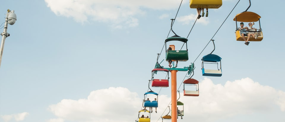 State fair attendees riding in colorful gondola booths.