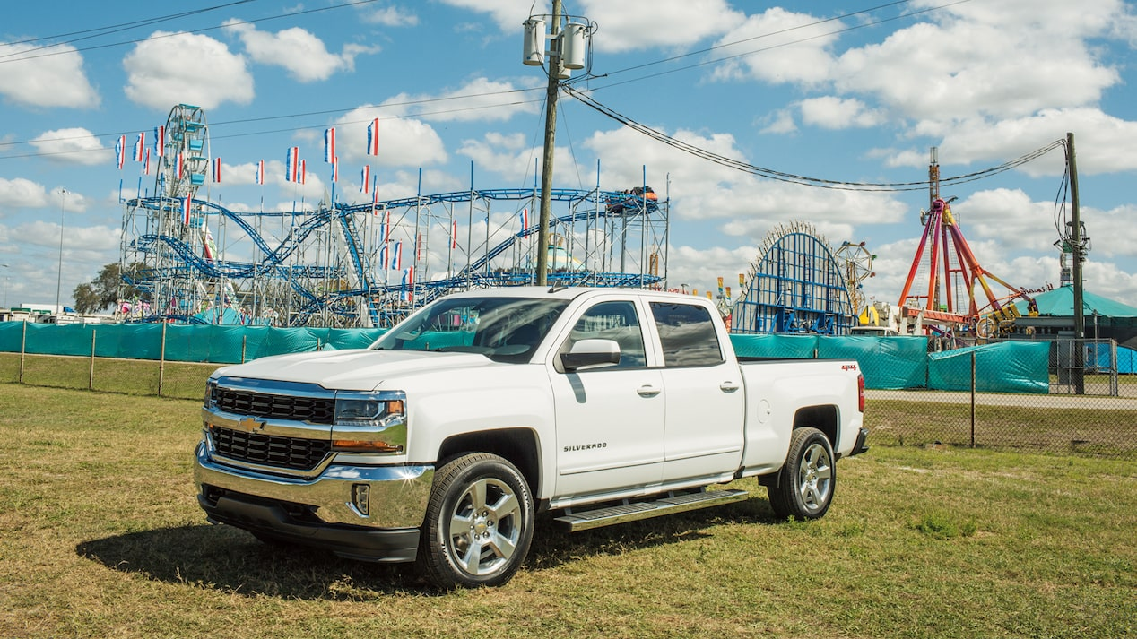 A Chevy Silverado parked with a state fair rollercoaster in the background.