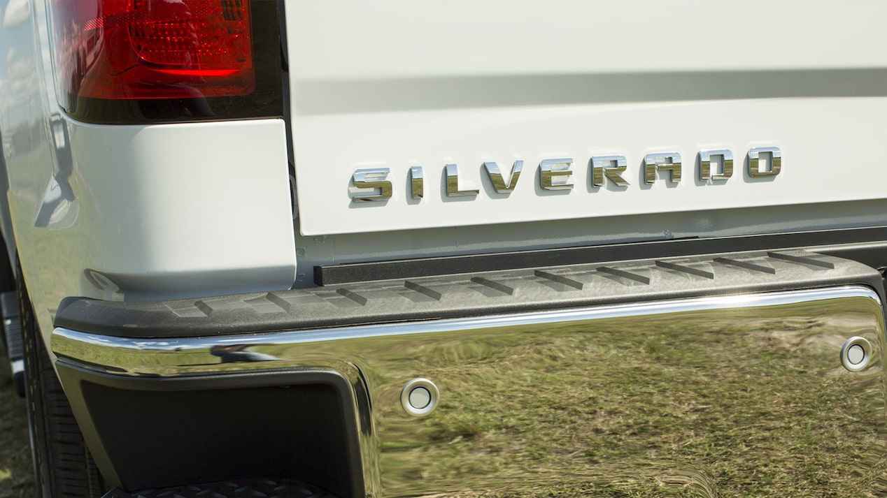 A close-up shot of the Silverado badge on a white truck's tailgate.