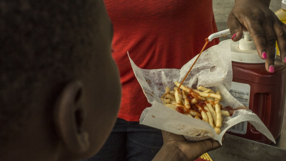 A young boy pumping ketchup onto piping hot fries.