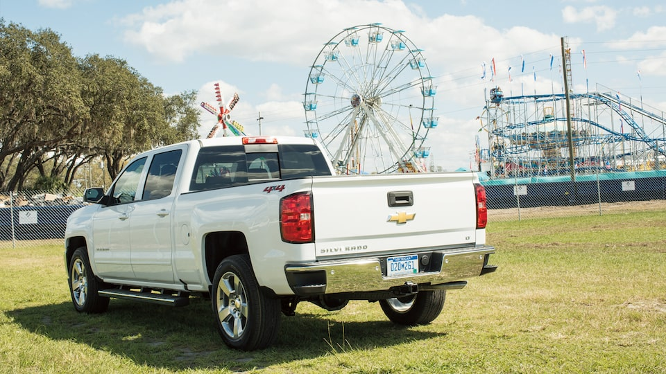 A Chevy Silverado parked with a Ferris wheel and rollercoaster in the background.